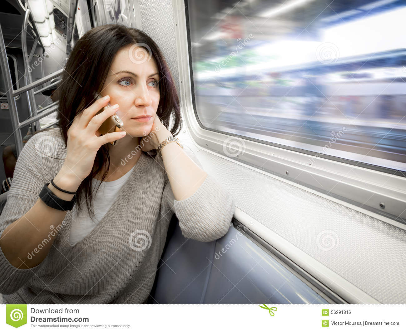 Woman in her 30s is riding the subway ans looking out the window