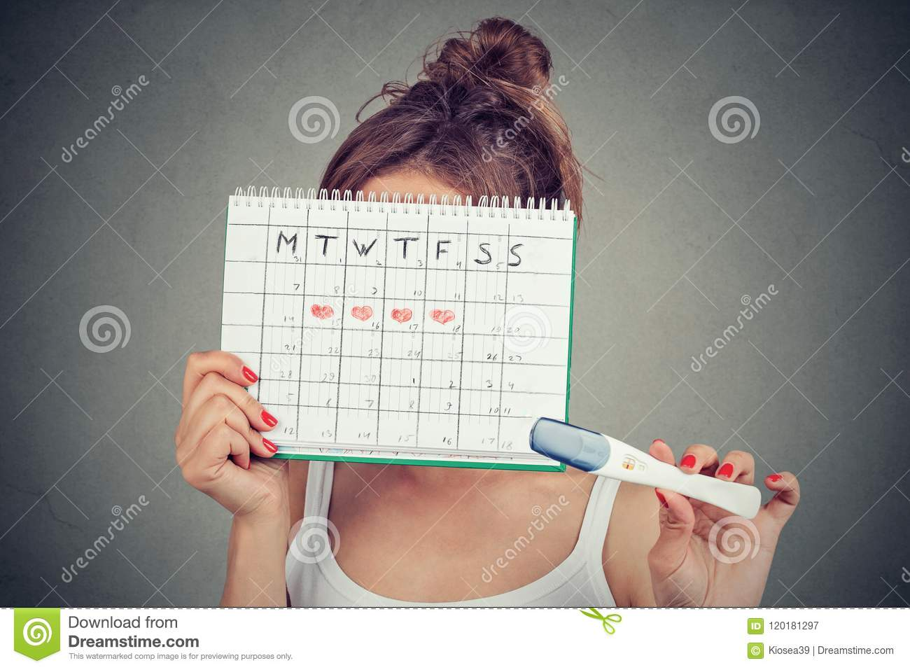 Woman hiding behind a periods calendar and showing a positive pregnancy test