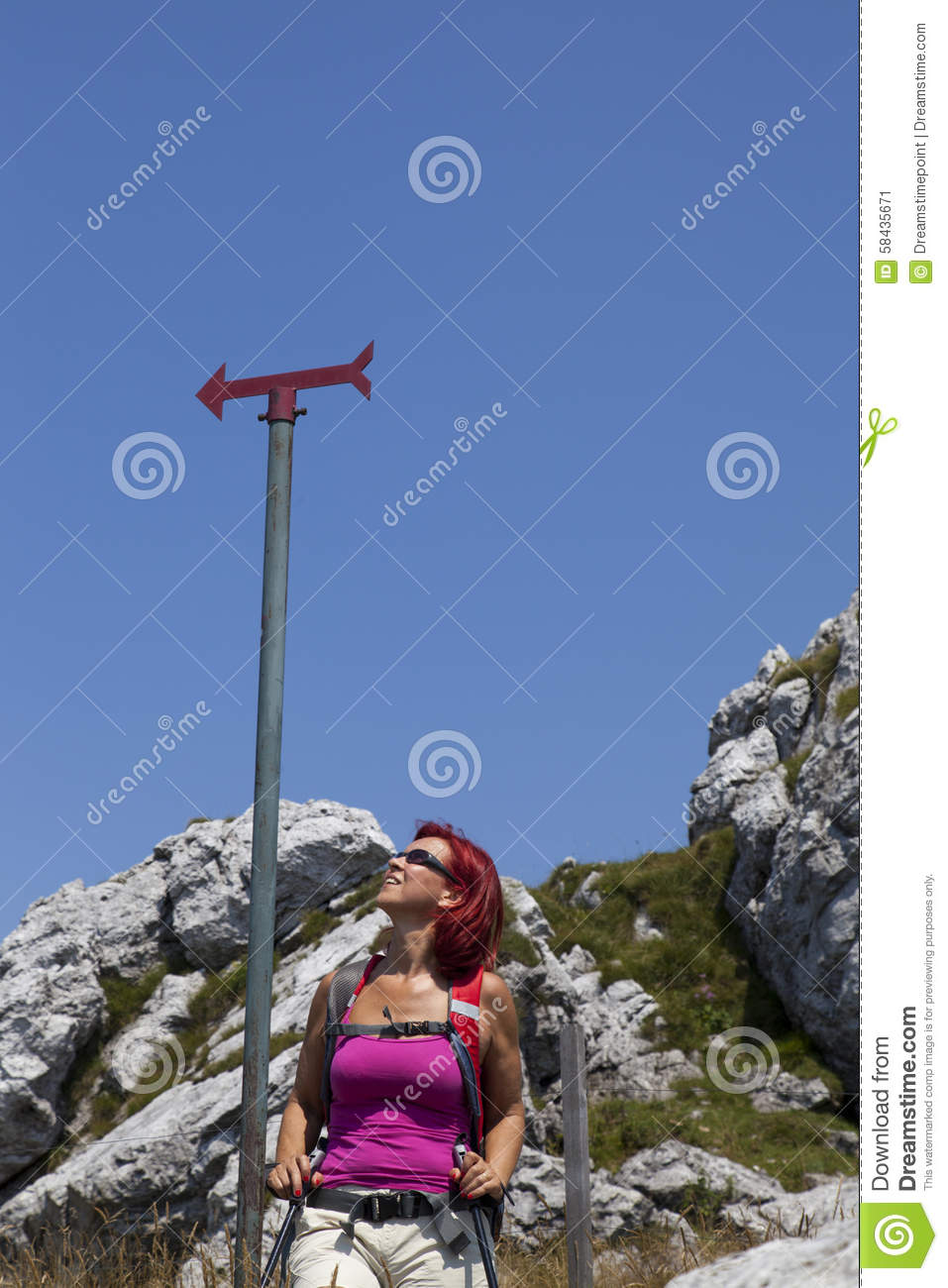 Woman hiker high in the the mountain resting under the sign post