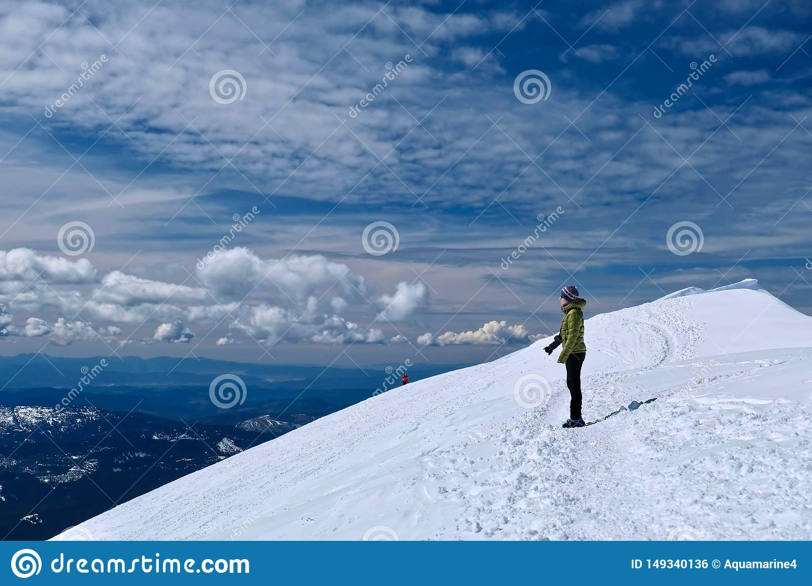 Woman hiker on mountain top looking at scenic view.