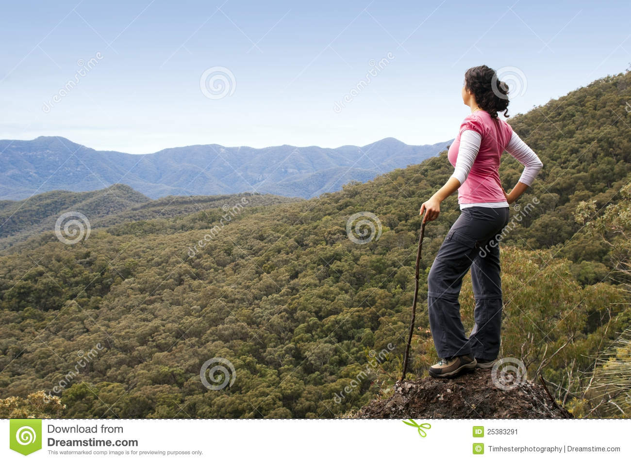Single female hiker looks out at view in mountains with forest below
