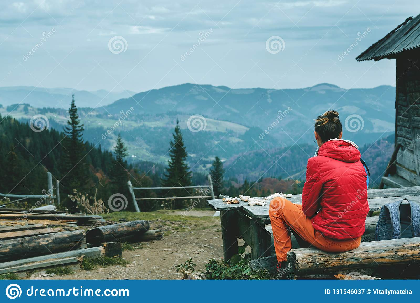 Woman hiker in red jacket and orange pants, sitting on the wooden bench near mountain hut with mountains on background