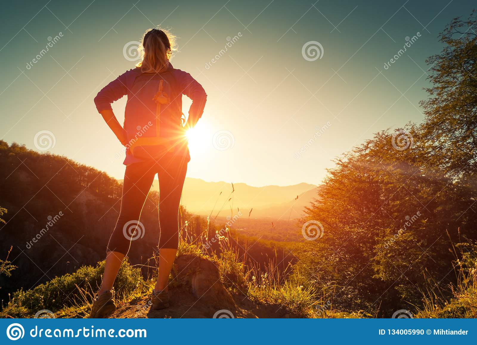 Woman hiker stands on the hill