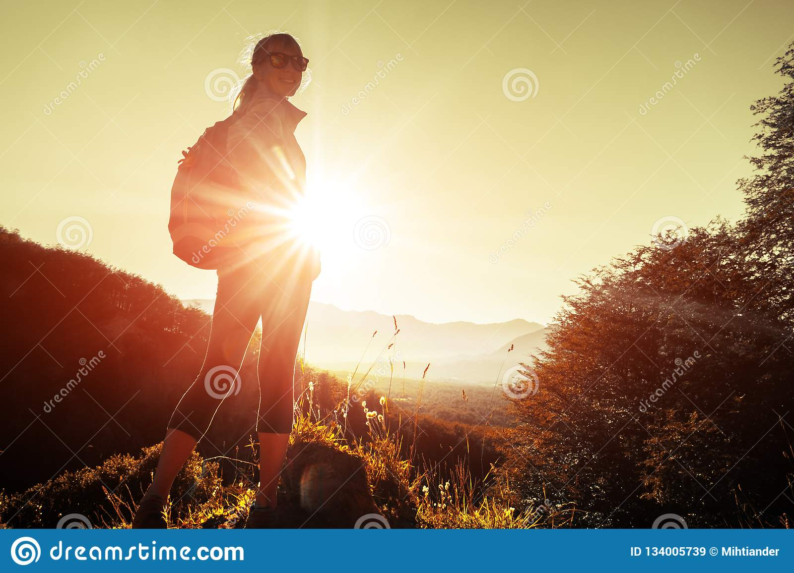 Woman hiker stands in mountains