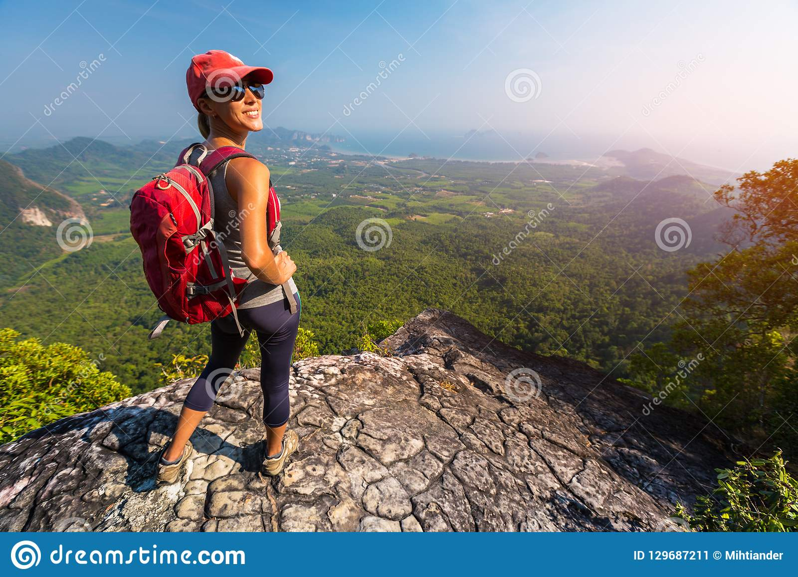 Woman hiker stands on top of the mountain