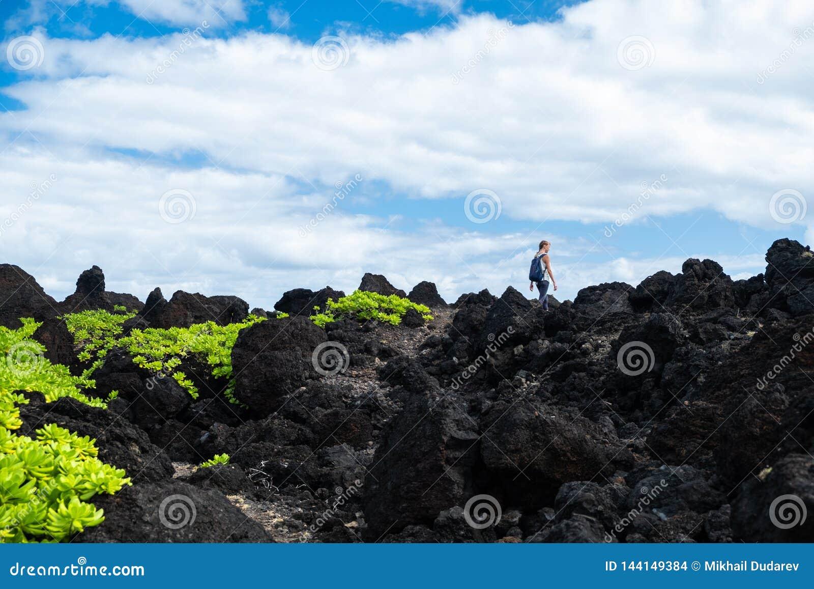 Woman hiker walks on the sharp volcanic land