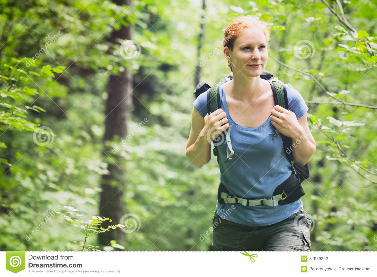 An active young woman hiking in a mountain forest by summer.
