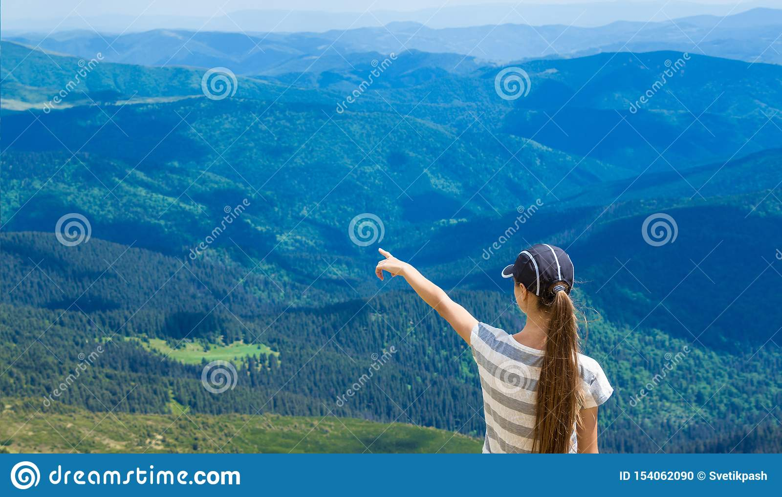 Woman hiking pointing to the sky enjoy the beautiful view at mountain