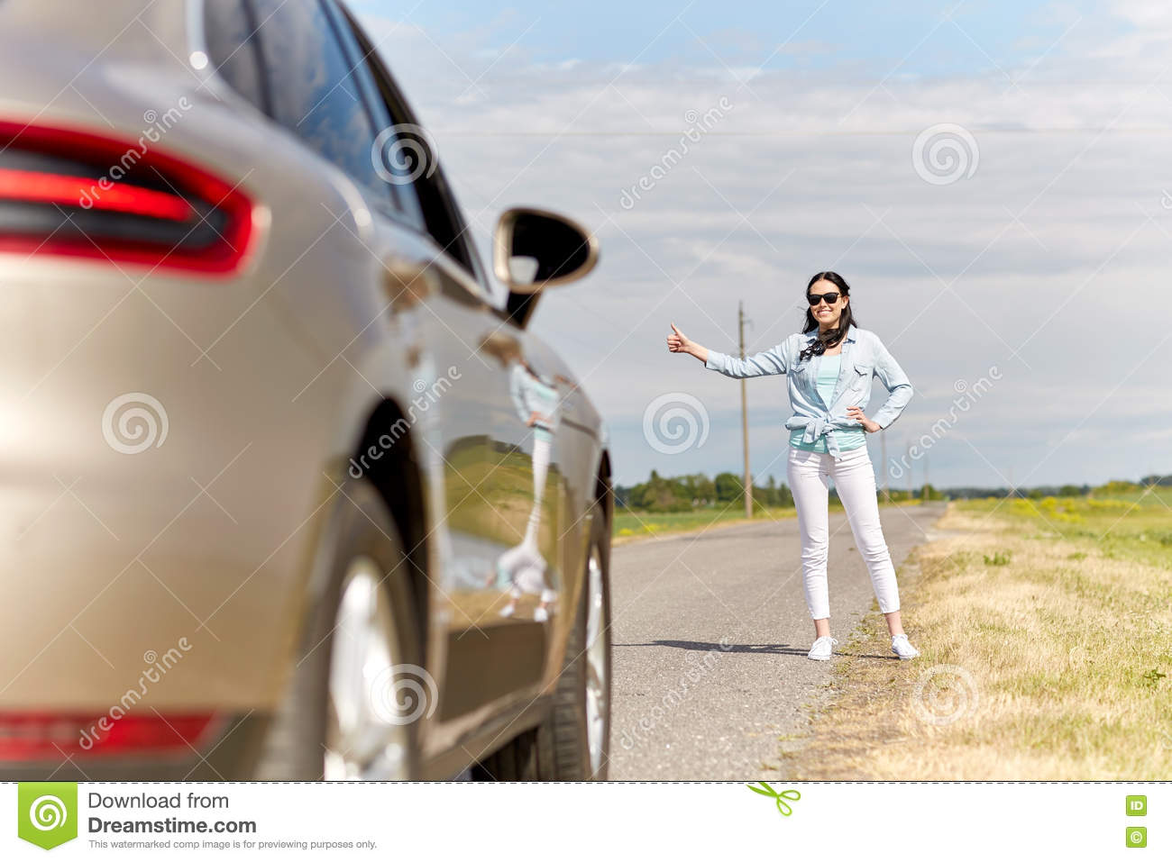 Woman hitchhiking and stopping car at countryside