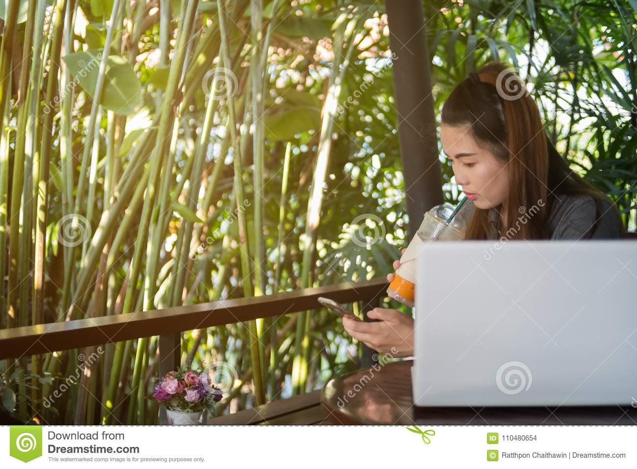 Woman hold mobile phone and drinking iced tea in coffee shop, la