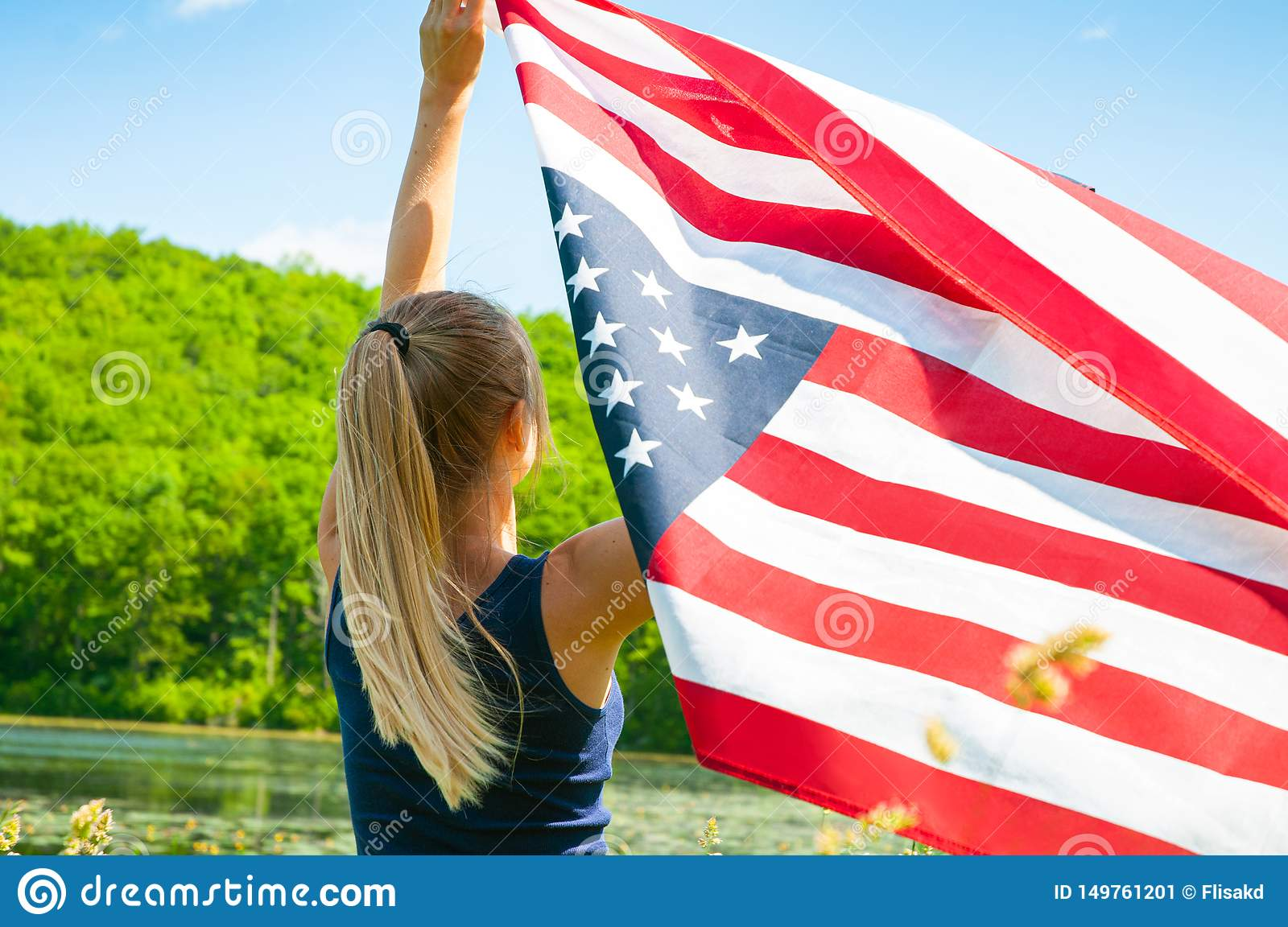 Woman holding American flag outdoors. United States celebrate 4th of July Independence Day