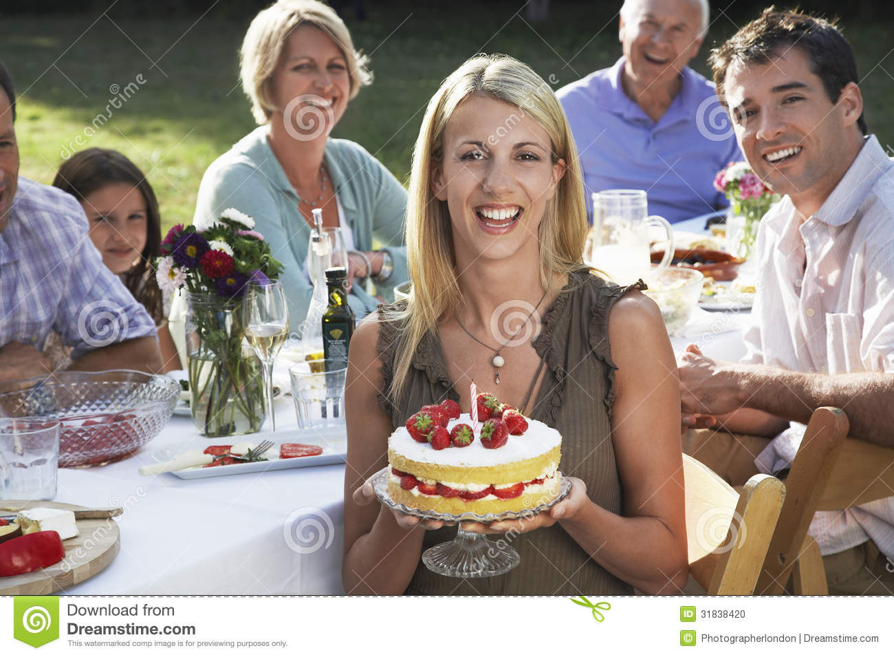 Woman Holding Birthday Cake With Family In Garden Stock