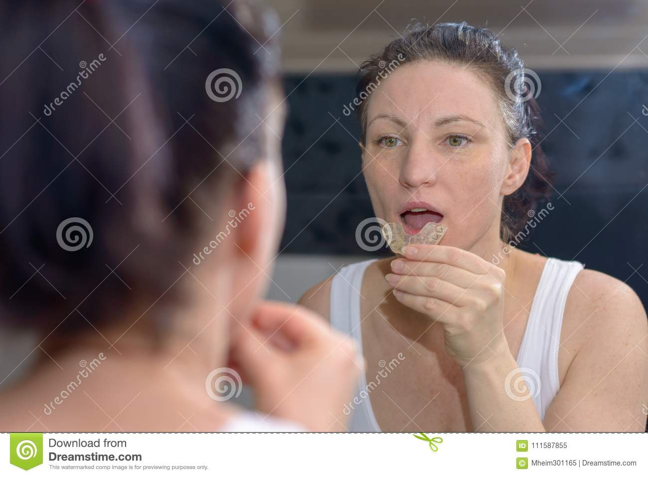 Woman holding a bite plate to prevent grinding