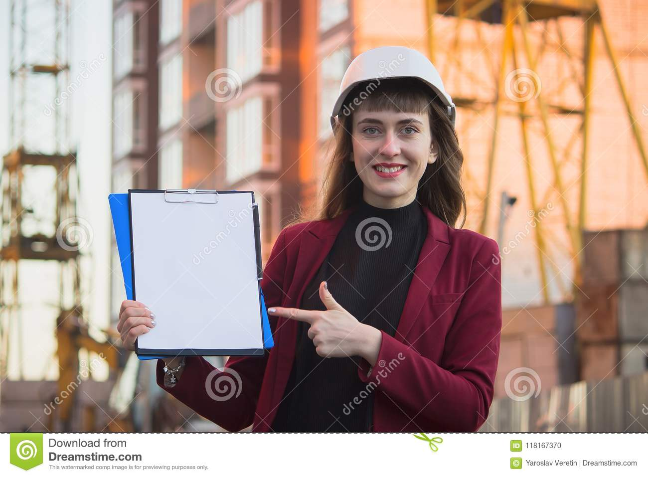 Woman holding blueprints, clipboard. Smiling architect in helmet at building