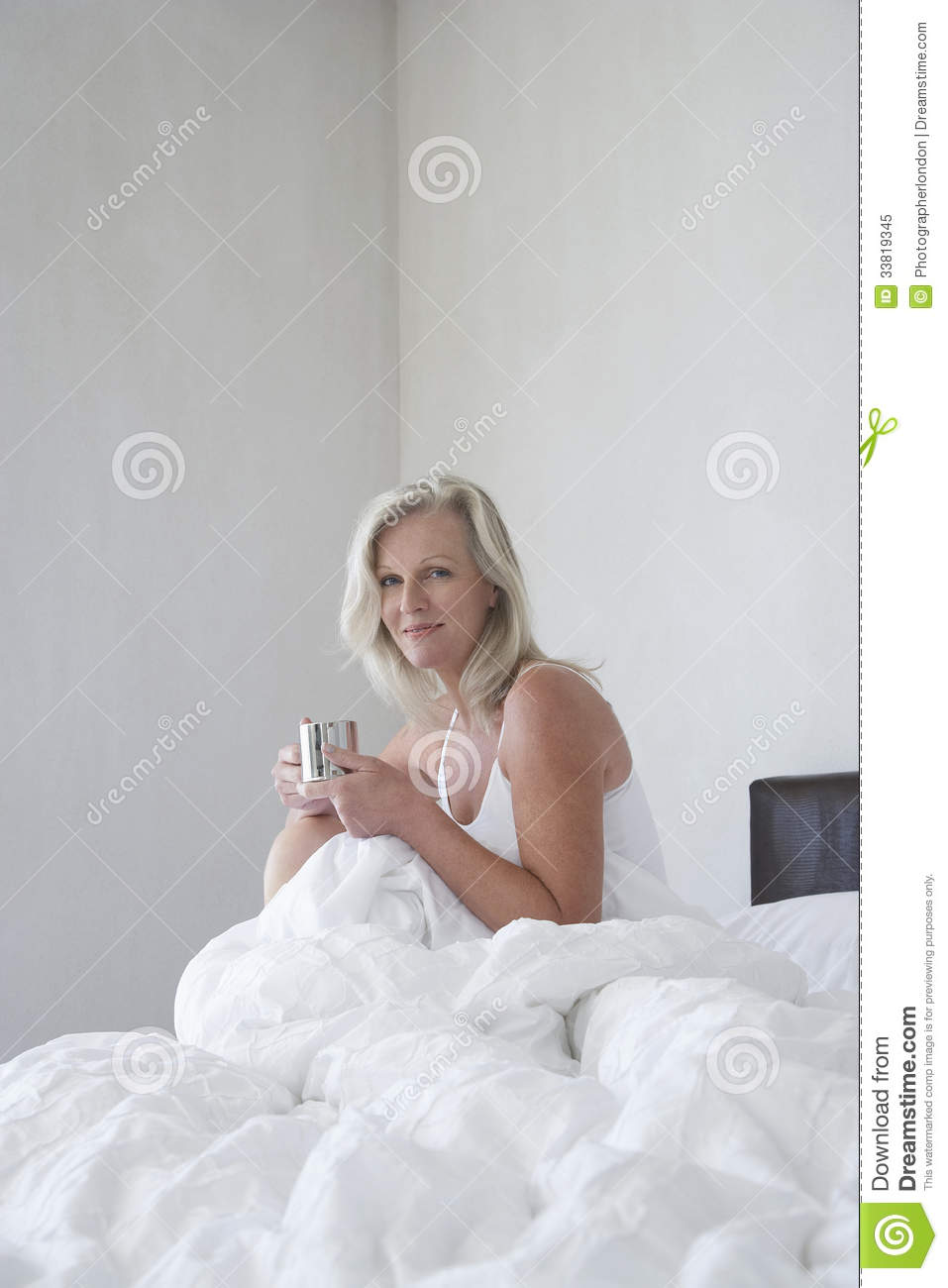 Woman Holding Coffee Cup On Bed Royalty Free Stock Photo