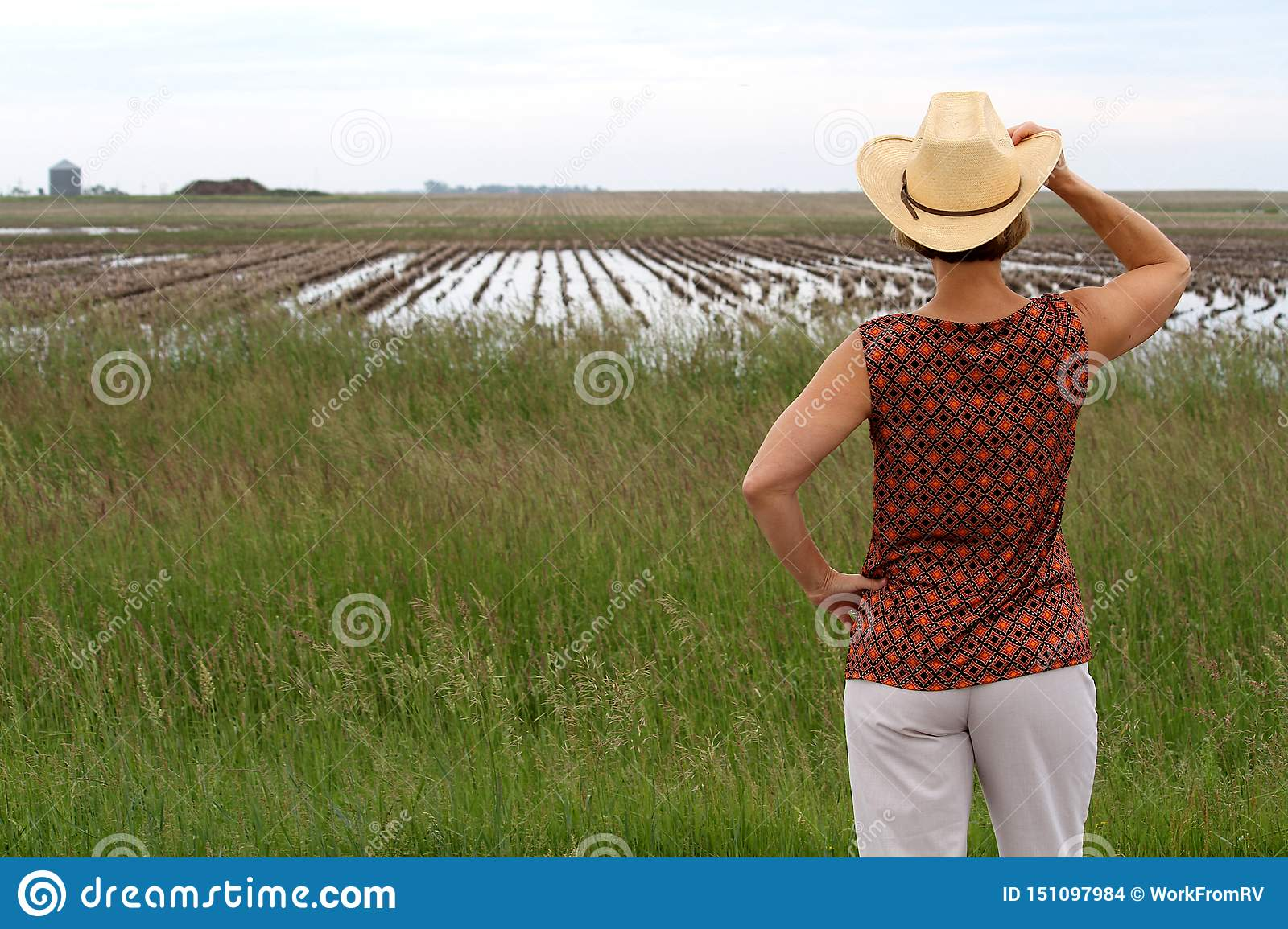 Woman holding cowboy hat looking at a farm field full of water.