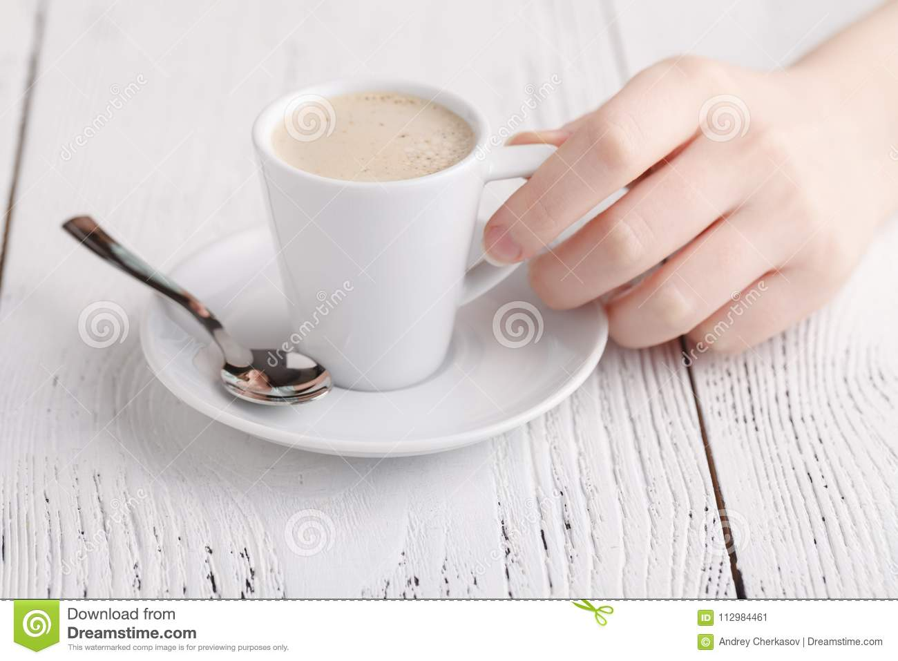 Woman is holding a cup of coffee