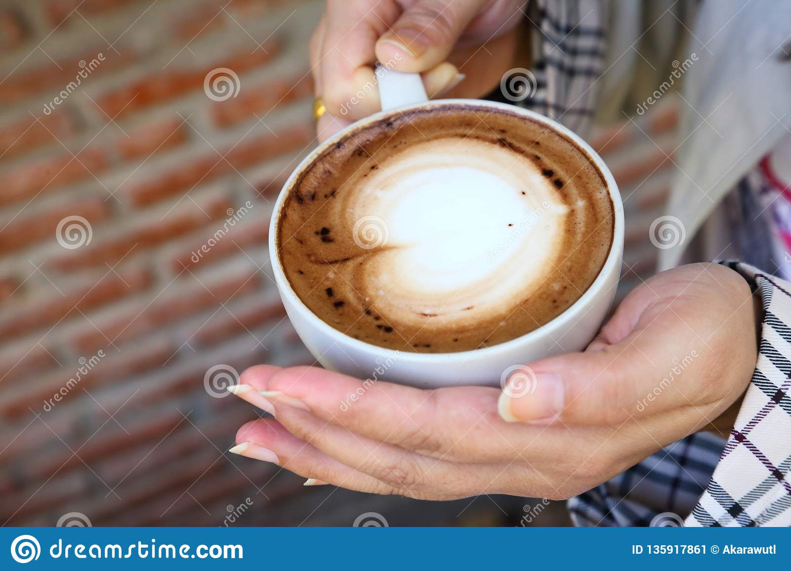 Woman holding cup of hot mocha coffee in her hand in the cafe during winter season