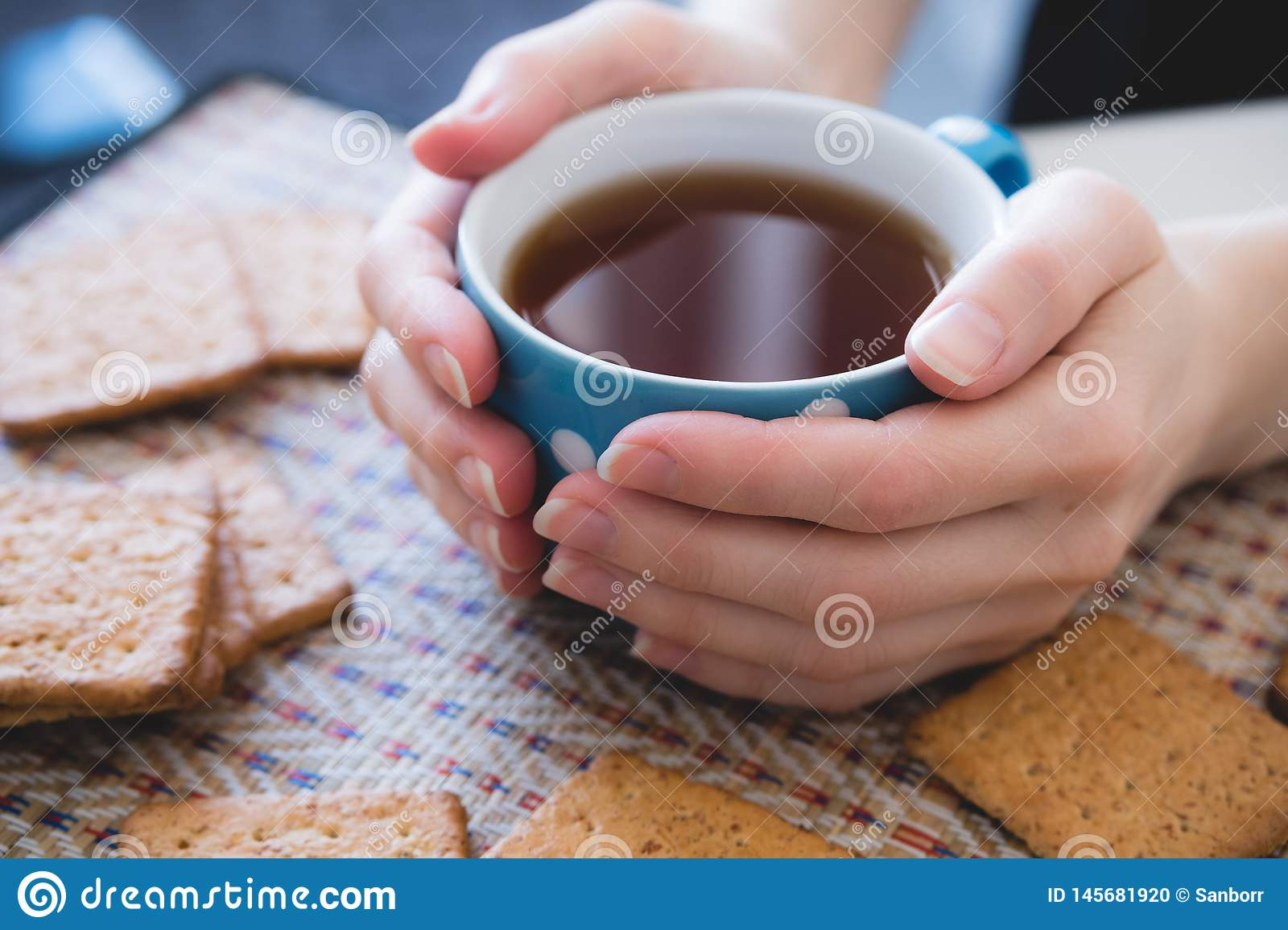 Woman holding a Cup of hot tea or coffee, lie next to cookies, close-up