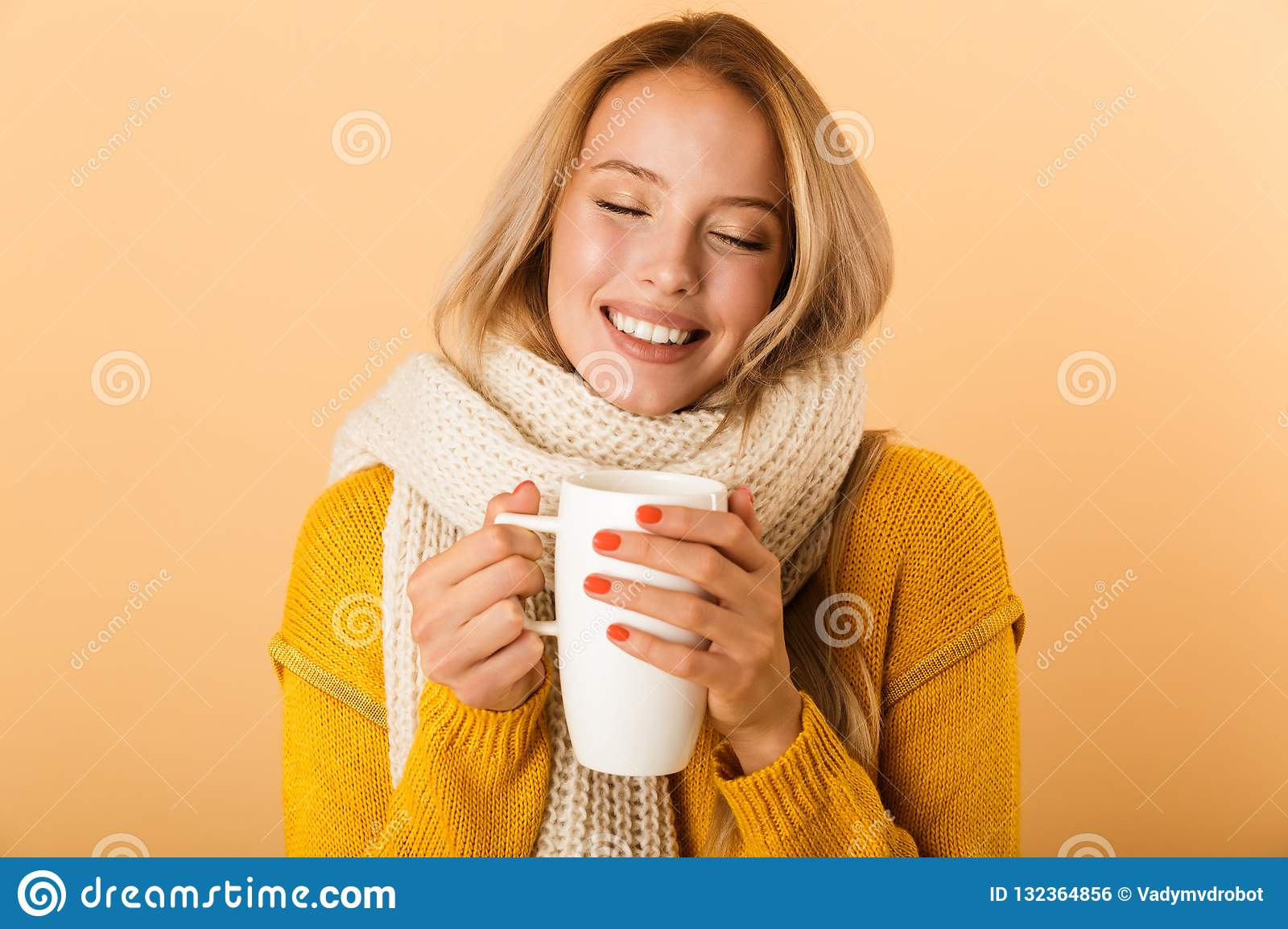Woman holding cup of tea wearing scarf posing isolated over yellow wall background