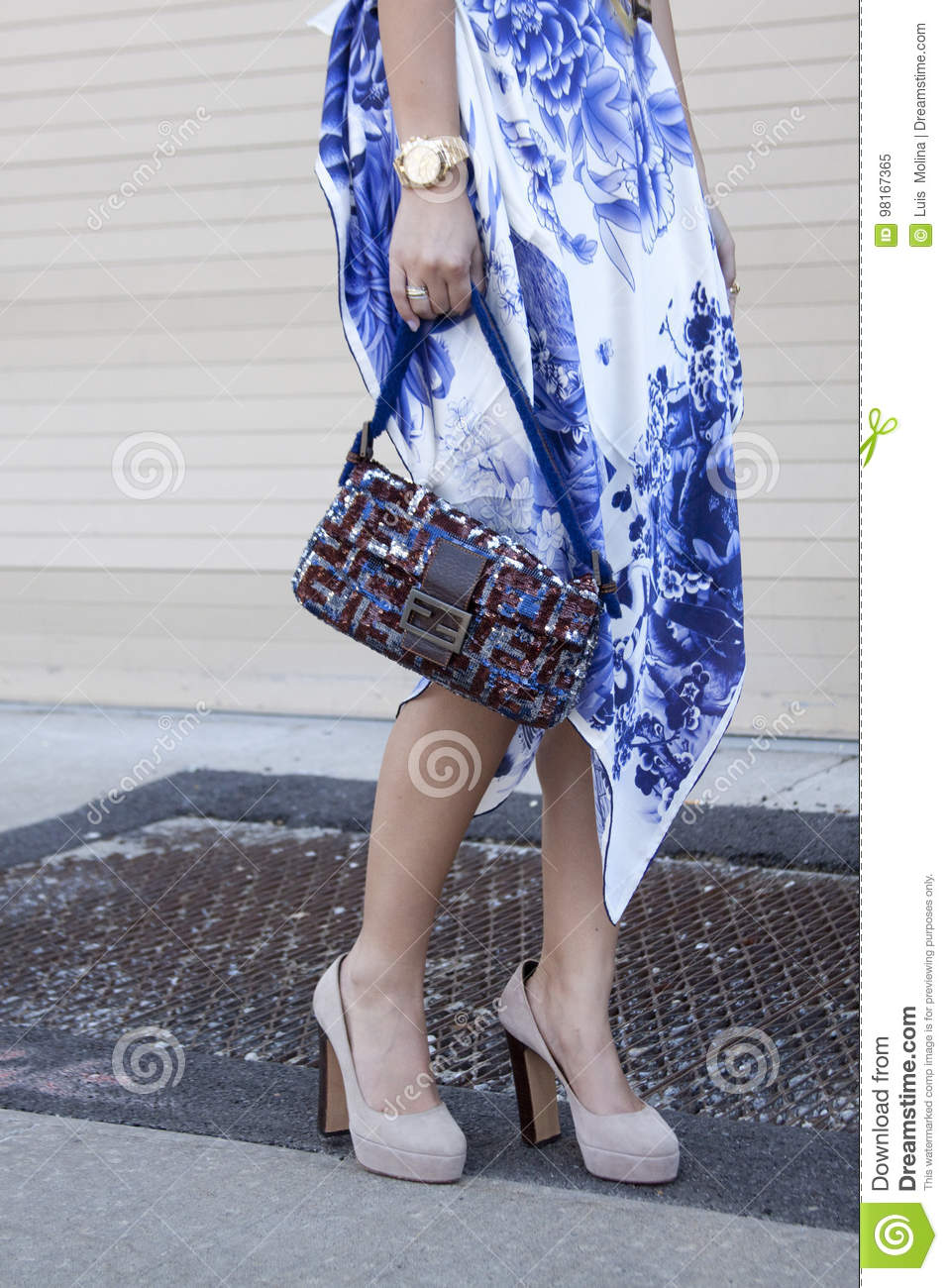 85531593b63a A Woman Holding A Designer Clutch Purse And Wearing High Heels ...