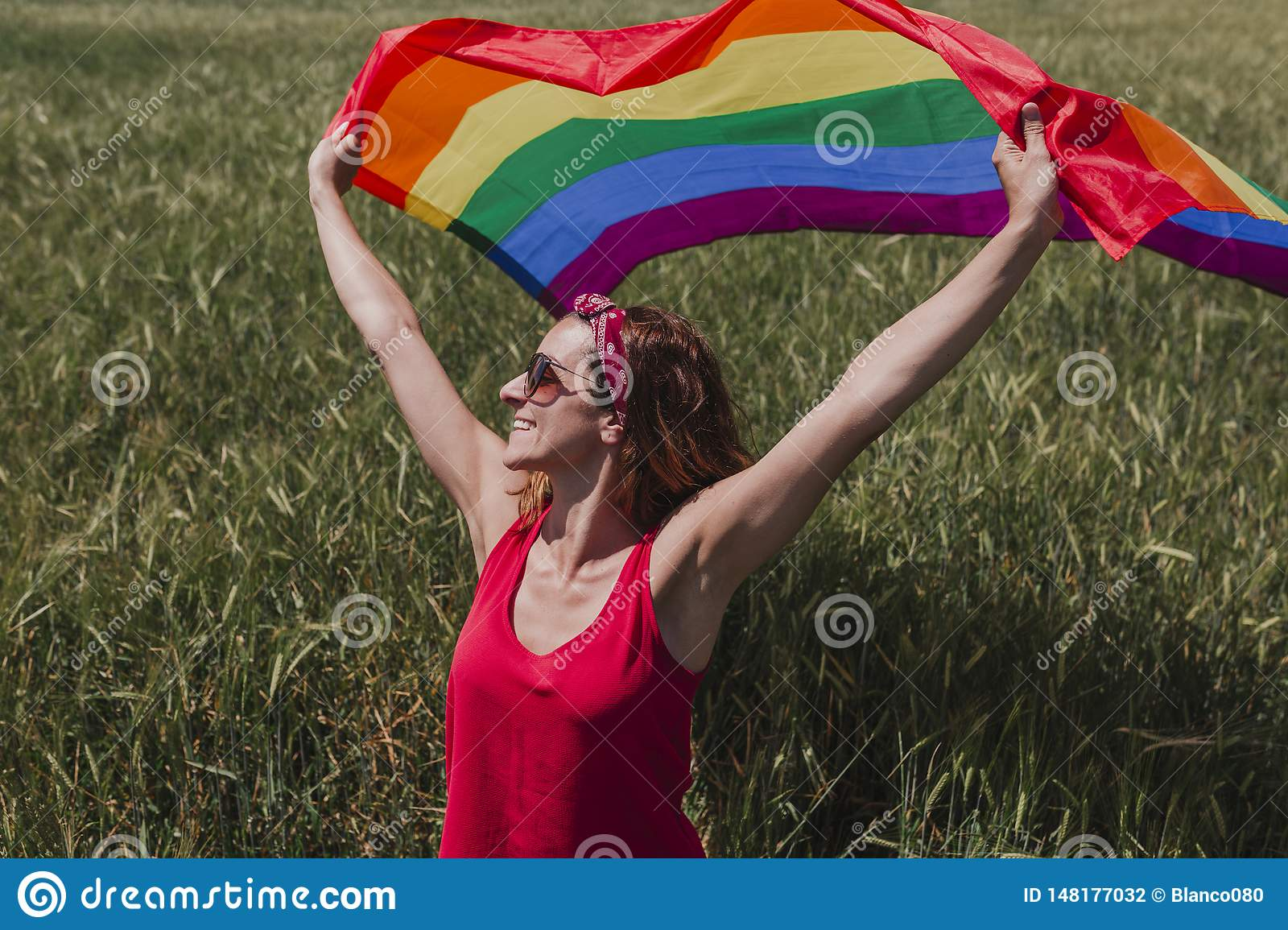 Woman holding the Gay Rainbow Flag on a green meadow outdoors. Happiness, freedom and love concept for same sex couples. LIfestyle