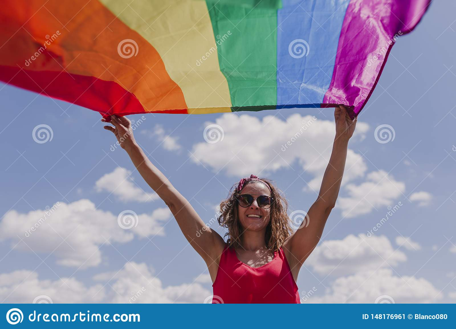 Woman holding the Gay Rainbow Flag over blue and cloudy sky outdoors. Happiness, freedom and love concept for same sex couples.
