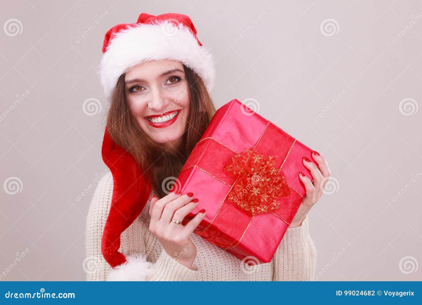bb699b24c4f8f Gorgeous woman wearing santa claus hat holding red big gift box with  ribbon. Xmas