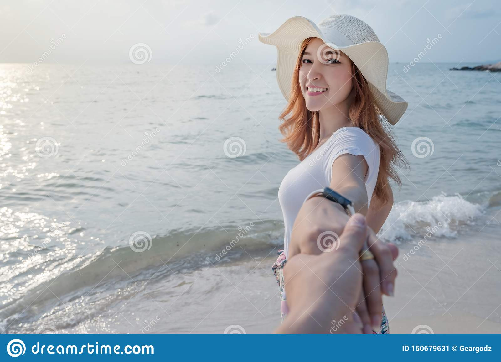 Woman holding hand of her boyfriend while leading to sea beach