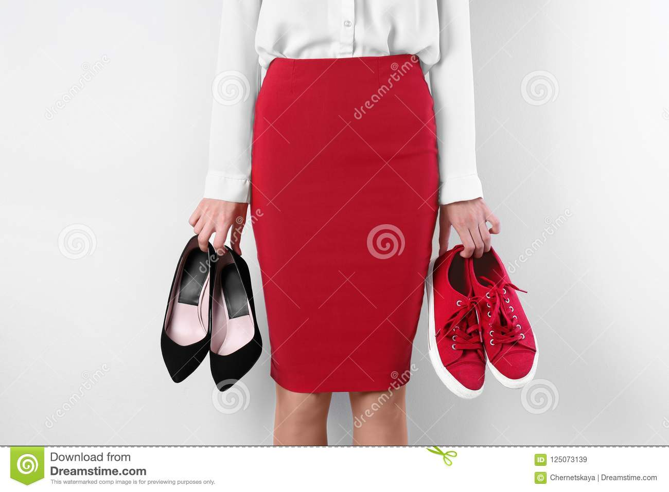 Woman holding high heeled shoes and sneakers on white background, closeup
