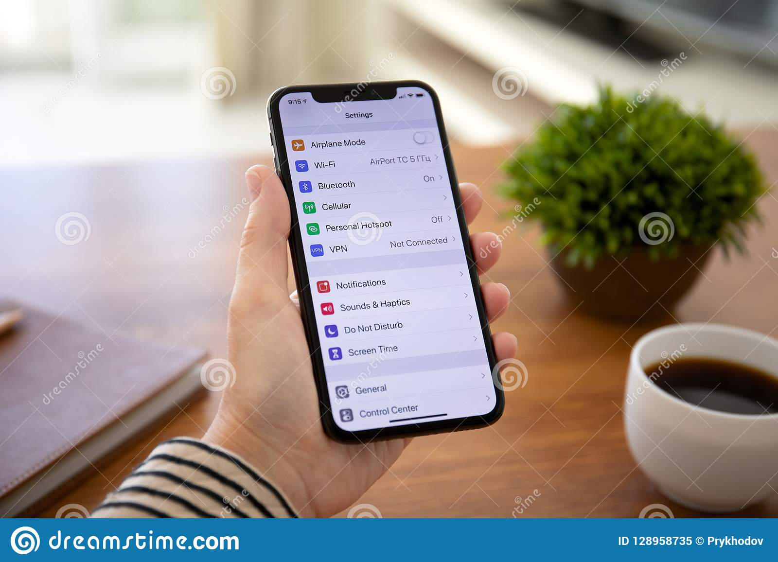 Woman holding iPhone X with Settings on the screen