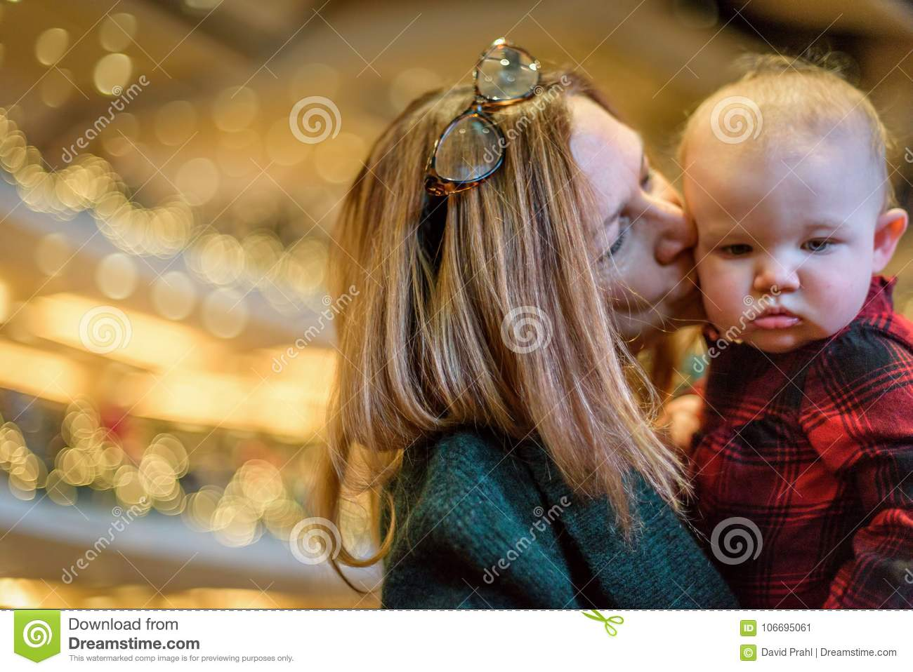 Woman kissing child in church on Christmas Eve