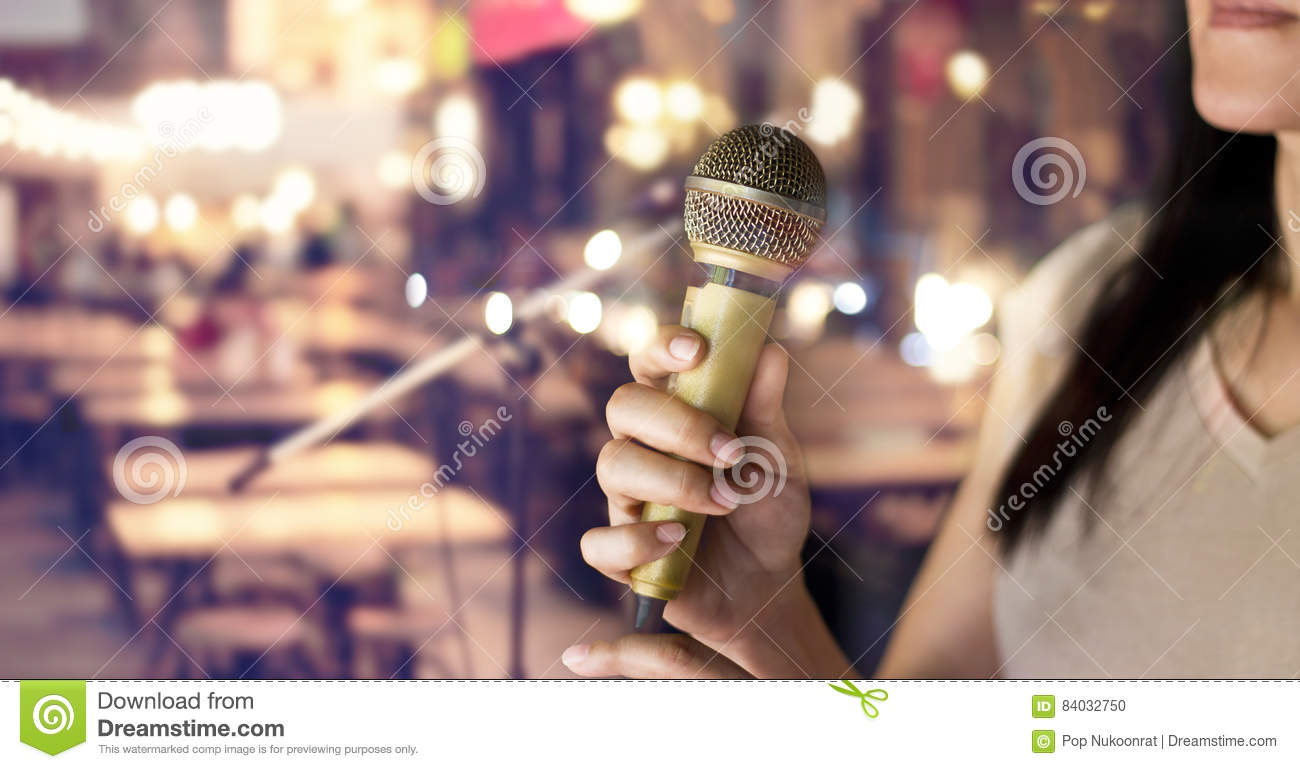 Woman holding microphone in hand on pub and restaurant