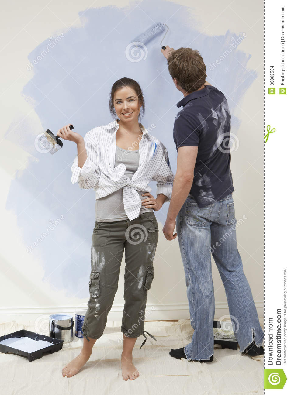 Woman Holding Paintbrush While Man Painting Wall Stock Photo