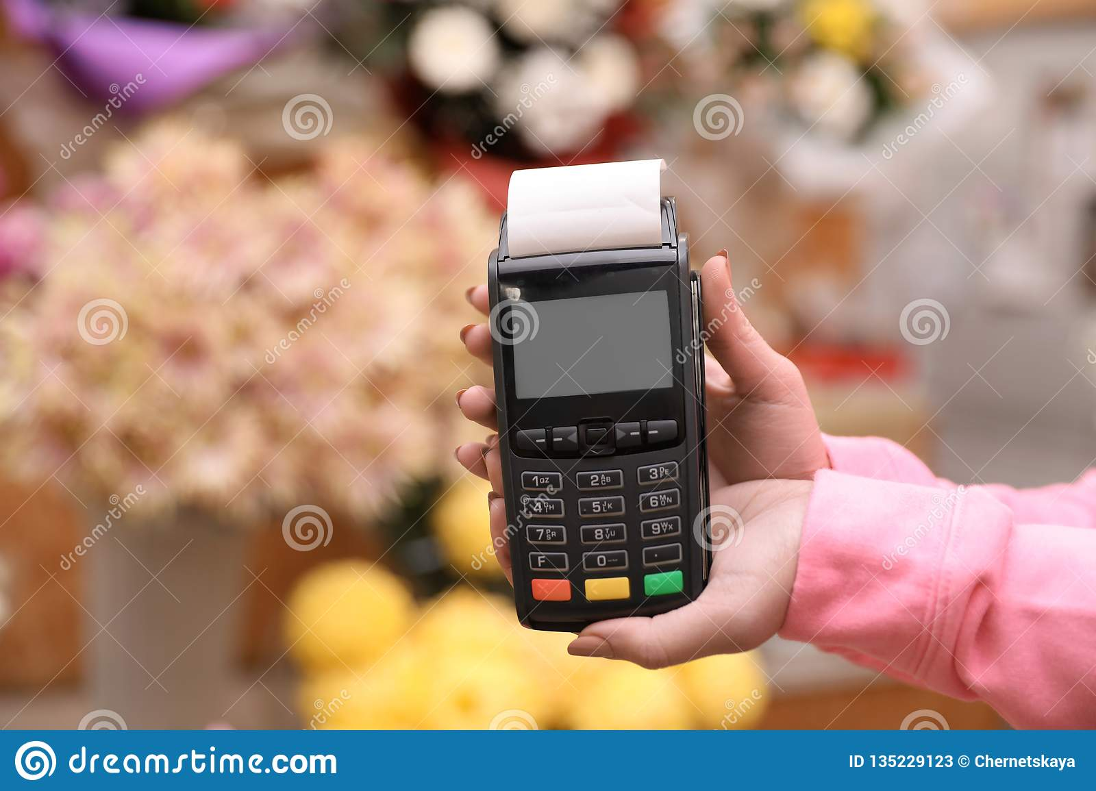 Woman holding payment terminal in floral shop, closeup.