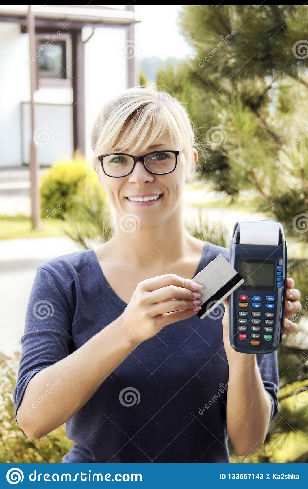 A woman is holding a payment terminal in the hands of the house. concept of buying a home and real estate
