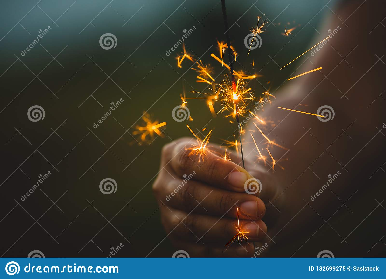 Woman holding and playing with fire sparklers on the festival