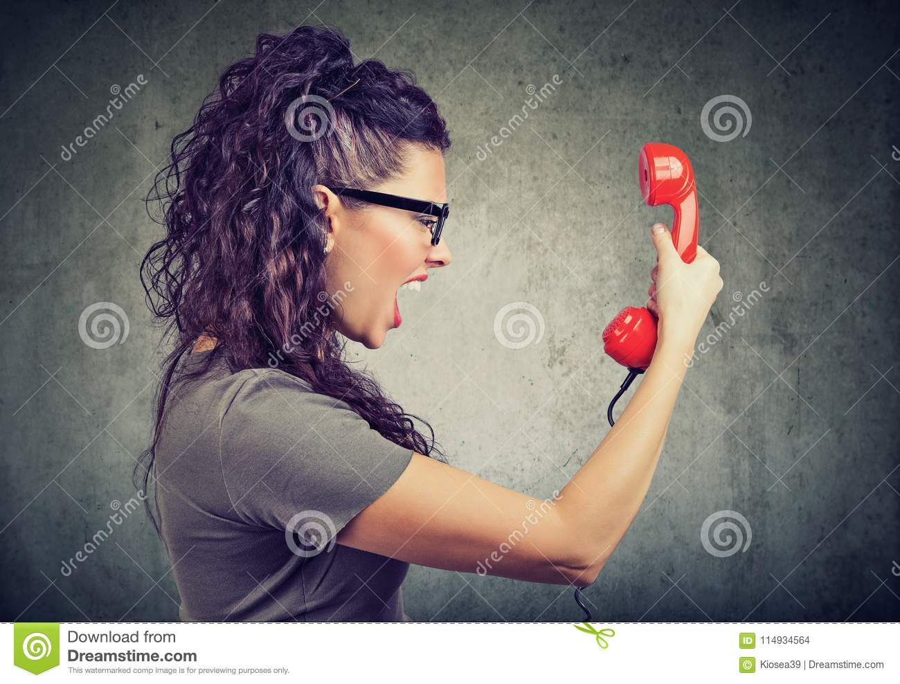 Woman holding red telephone receiver and yelling in anger.