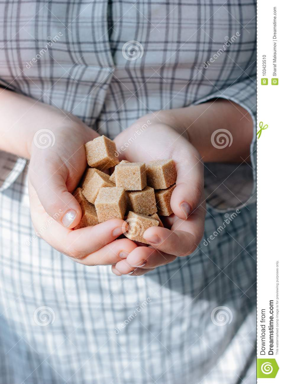 Woman holds brown sugar cubes in hands.