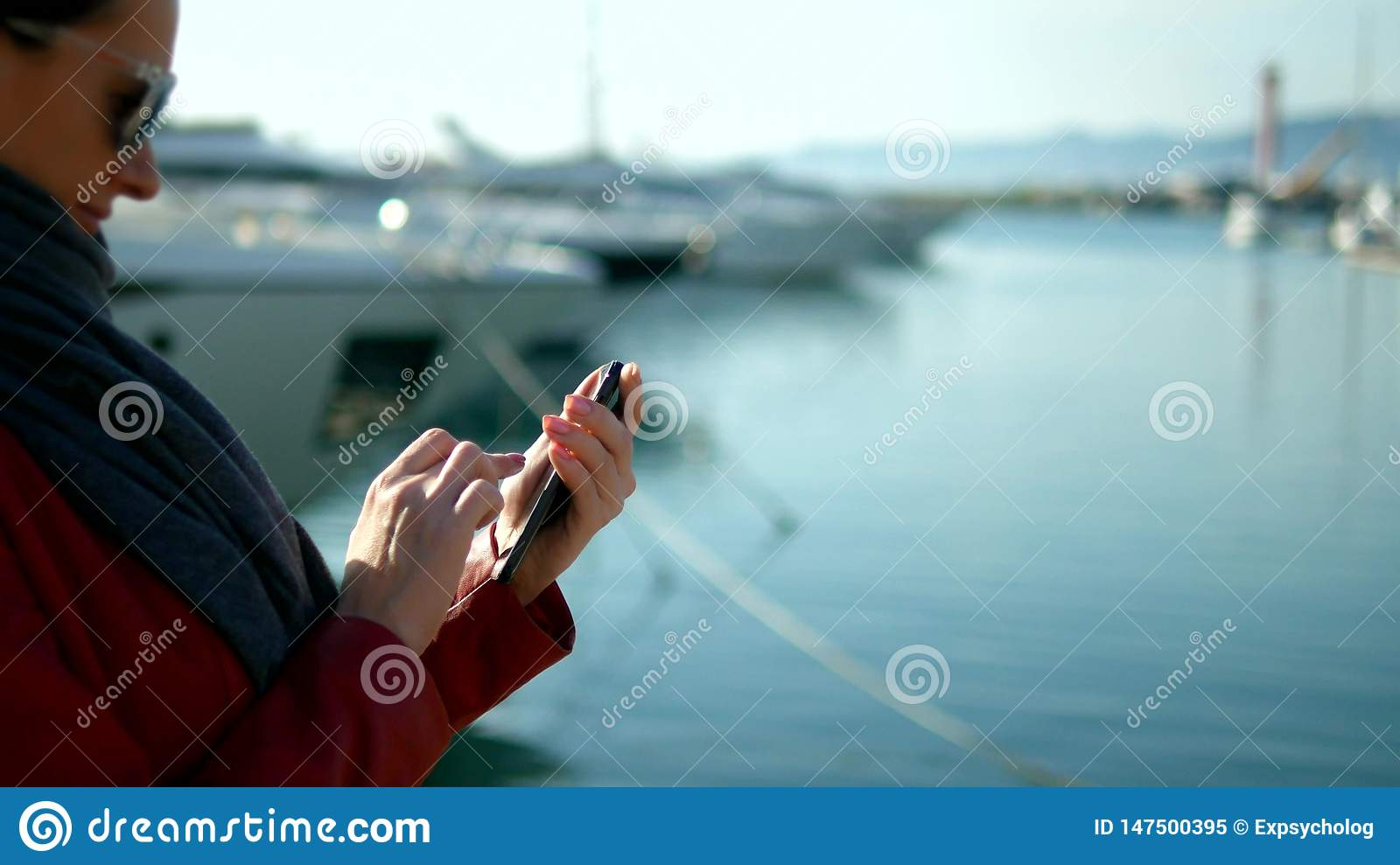 Woman holds smartphone on blurred background of port with yachts