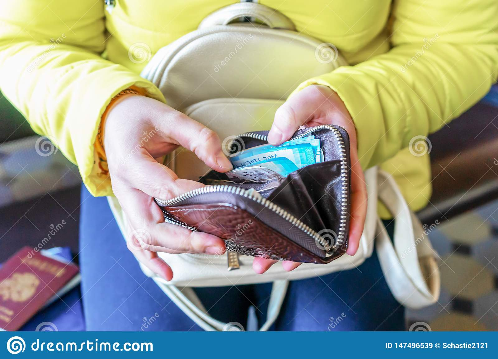 A woman holds a wallet and counts Russian money.