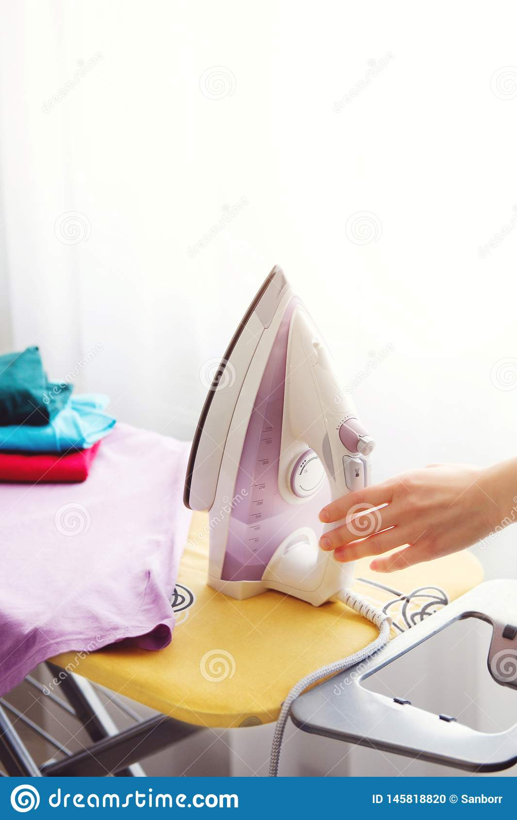 The woman the housewife irons clothes at home. On the Ironing Board iron and purple t-shirt, as well as other things of different