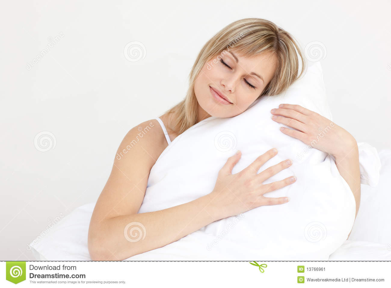 Woman Hugging Her Cushion Sitting On Her Bed Stock Image