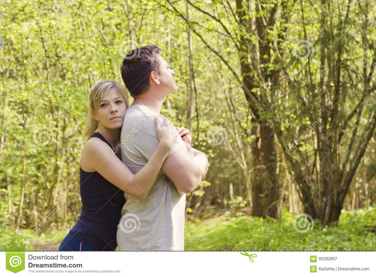 Woman hugs a man who is standing with her back to her. The concept of family problems, forgiveness