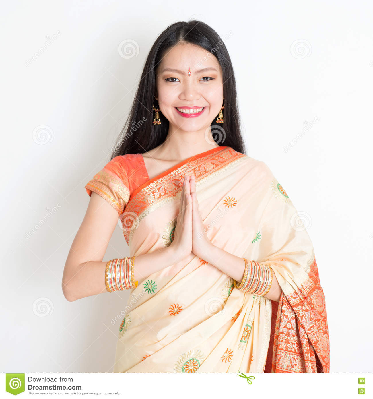 c05ada179b Portrait of mixed race Indian Chinese girl with traditional sari dress in  greeting gesture, standing on plain background.