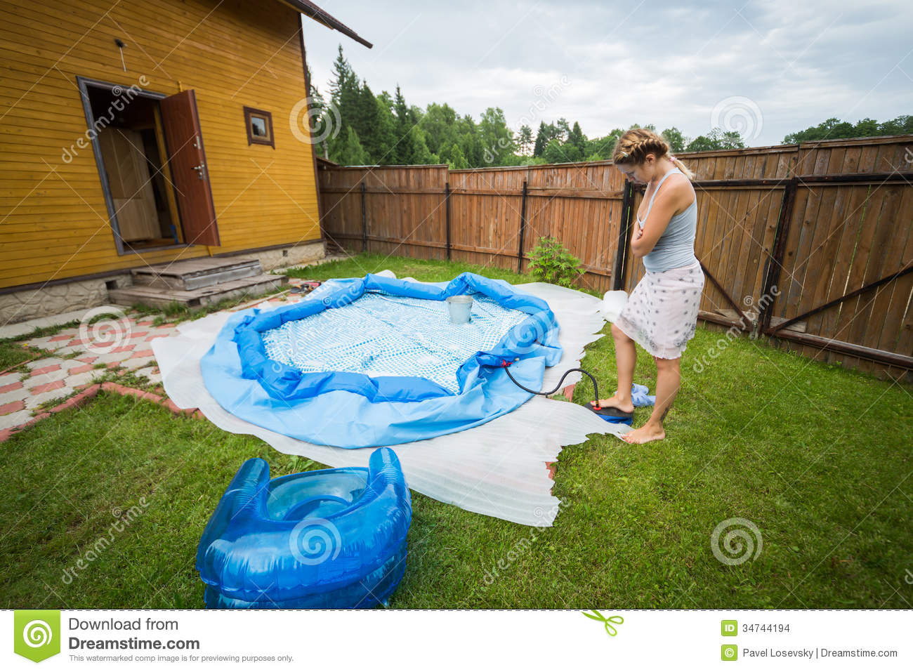 Woman inflates inflatable swimming pool