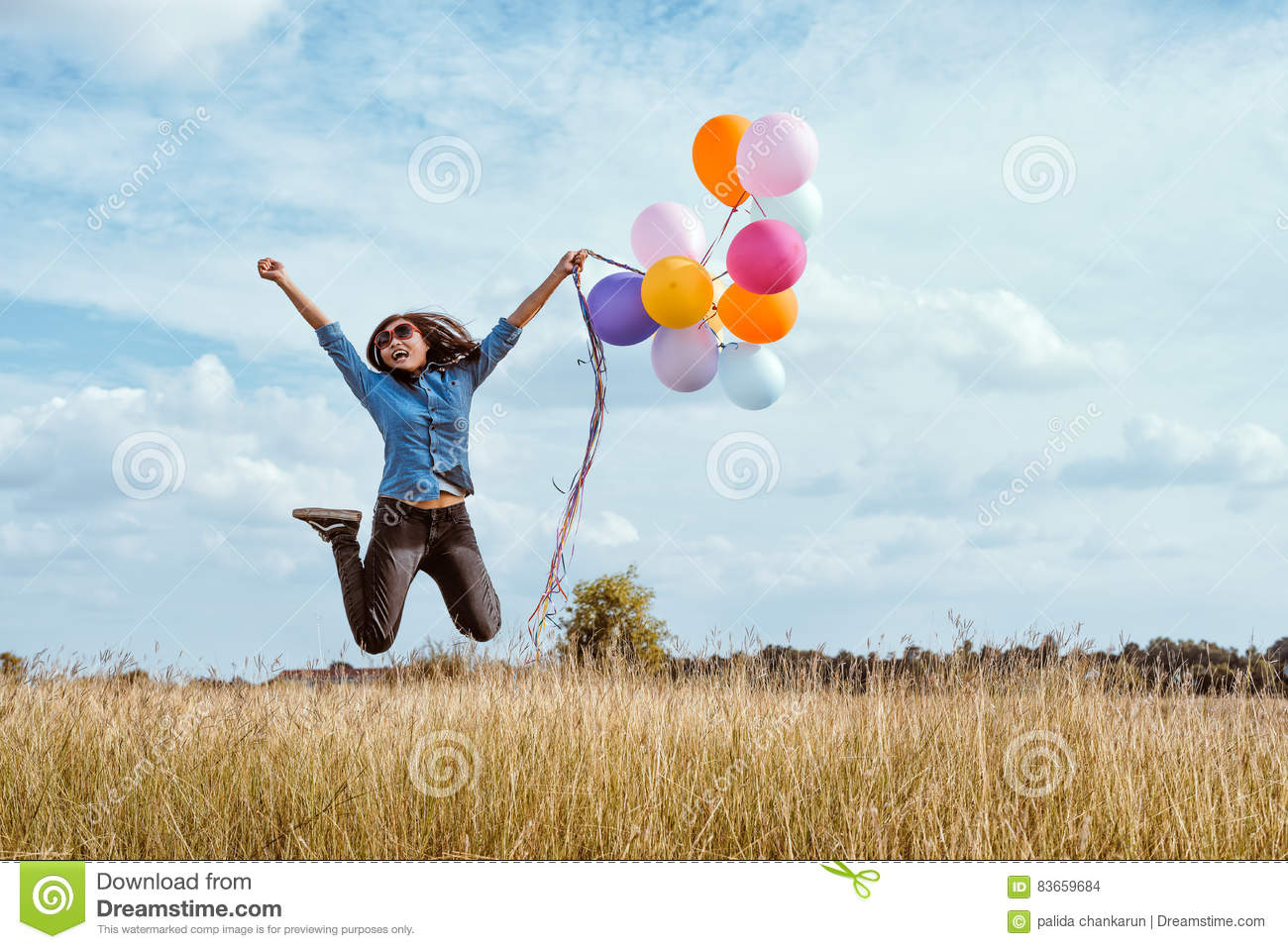 Woman jumping with colorful balloons in the meadow