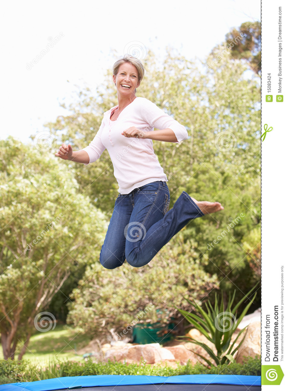 Woman Jumping Trampoline In Garden Stock Image
