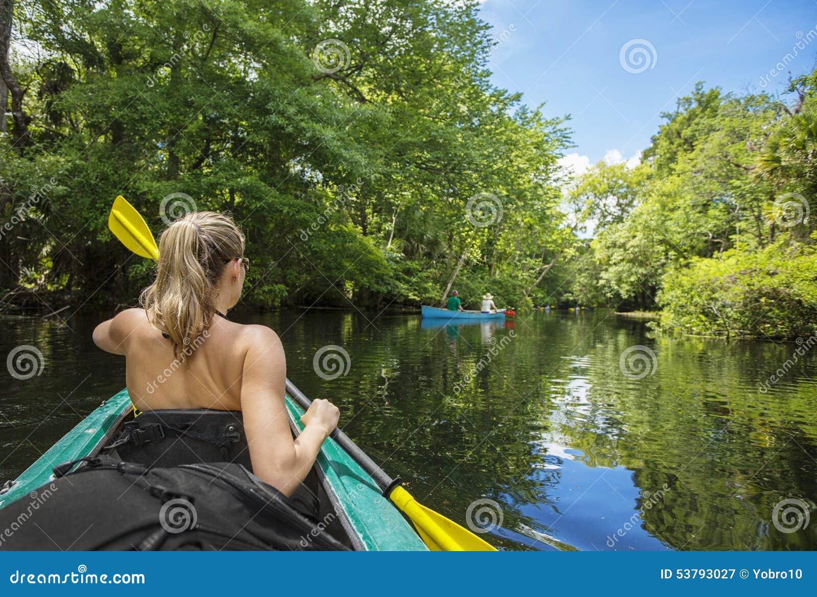 Woman Kayaking Down A Beautiful Tropical Jungle River