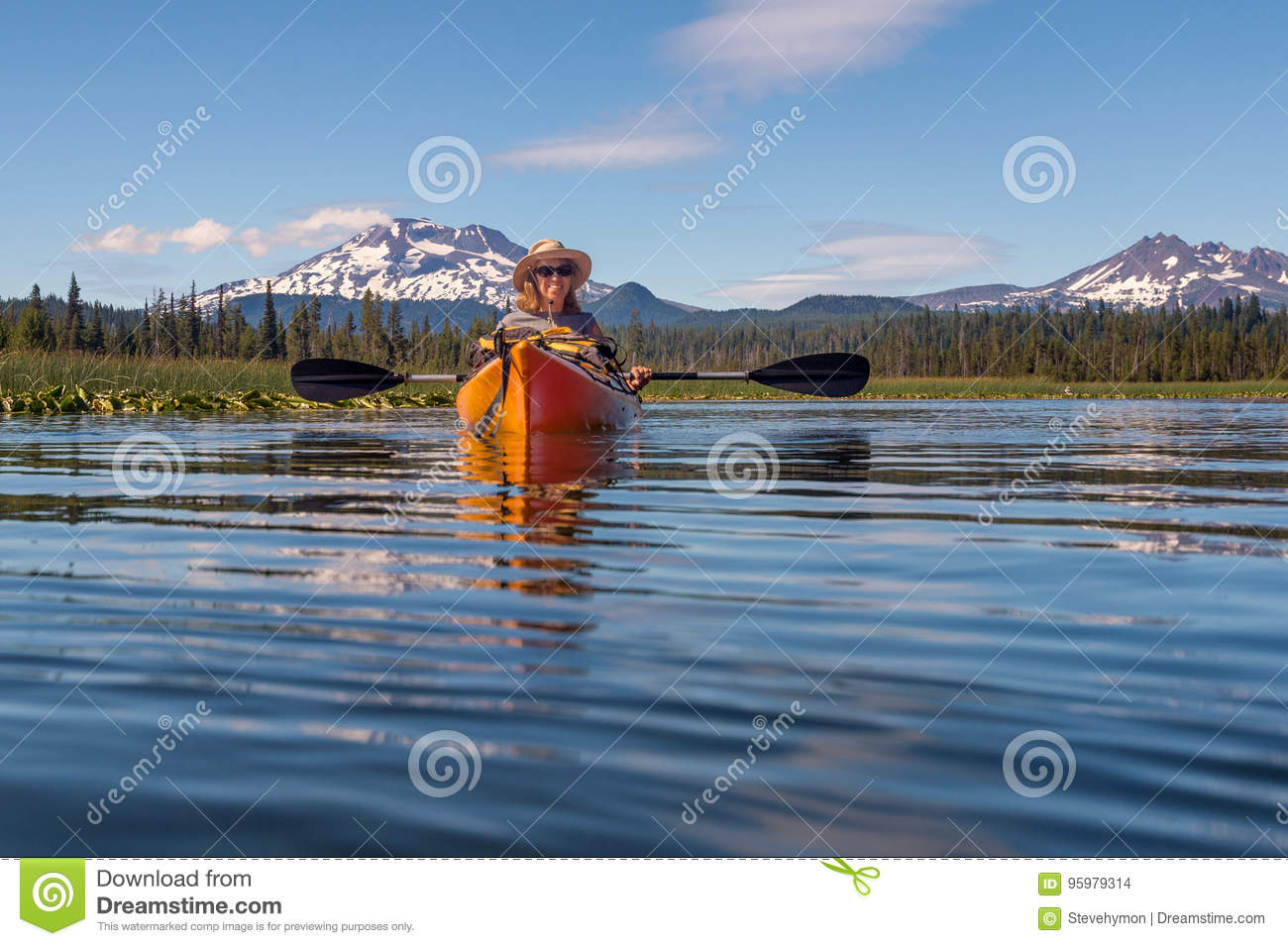 Woman kayaking on mountain lake near Bend, Oregon